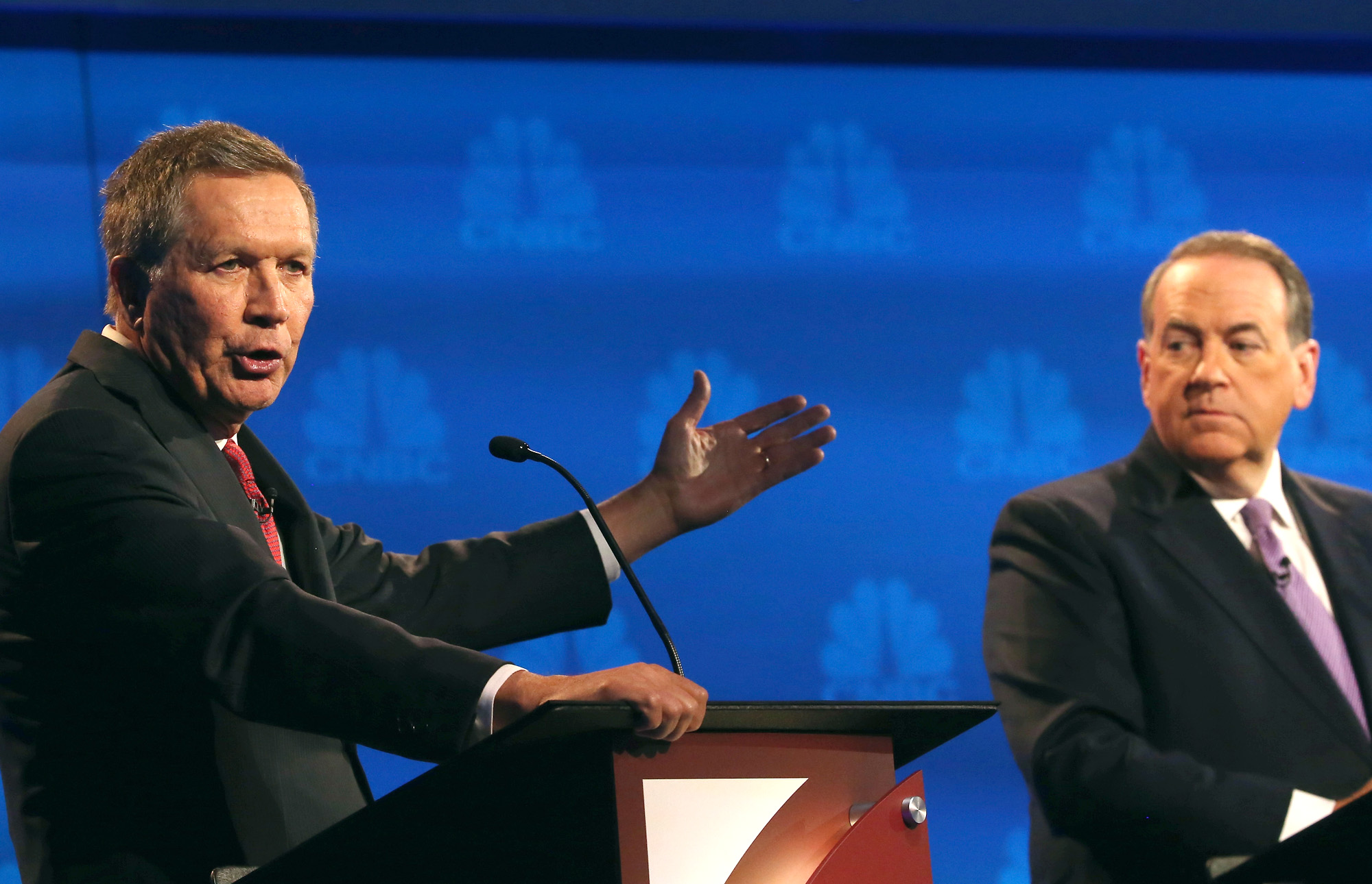 BOULDER, CO - OCTOBER 28: Presidential candidates Ohio Governor John Kasich (L-R) speaks while Mike Huckabee looks on during the CNBC Republican Presidential Debate at University of Colorados Coors Events Center October 28, 2015 in Boulder, Colorado. Fourteen Republican presidential candidates are participating in the third set of Republican presidential debates. (Photo by Justin Sullivan/Getty Images)