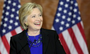 Image of Hillary Clinton smiling in front of two American flags