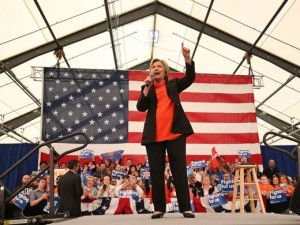 Hillary Clinton standing on stage in a black pantsuit with red shirt with a microphone in front of a large American flag with supporters in the background