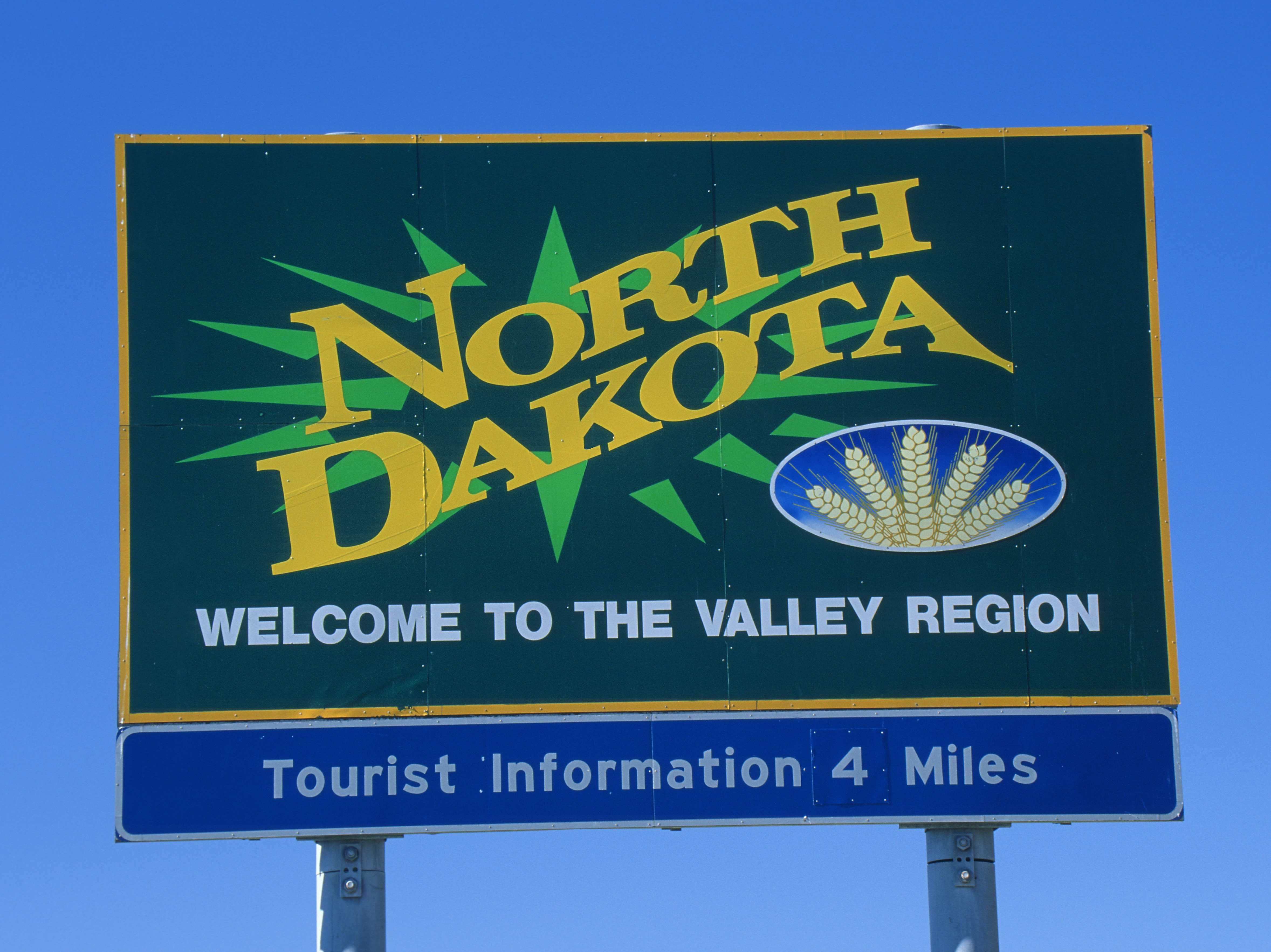 Green sign with text: North Dakota: Welcome to the Valley Region / Tourist Information: 4 Miles