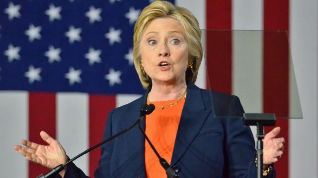 Close-up of Hillary Clinton talking behind a podium in front of a large American flag