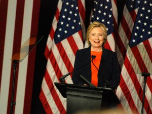 Hillary Clinton talking behind a podium in front of several American flags