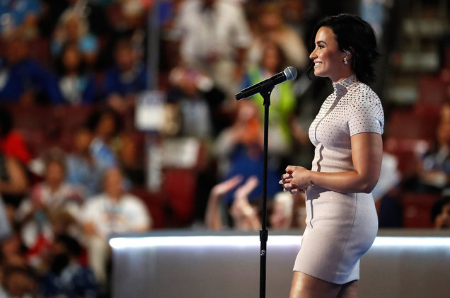 Side view of Lovato wearing a beige dress talking into a floor microphone