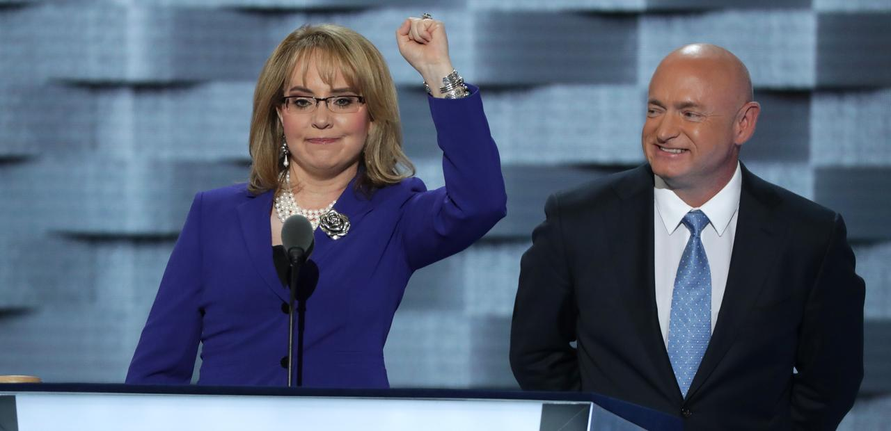 Image of Gabby Giffords raising left arm enthusiastically with husband Mark Kelly standing next to her