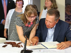Anne Gerhardt, standing, leans over Kasich as he signs the bills