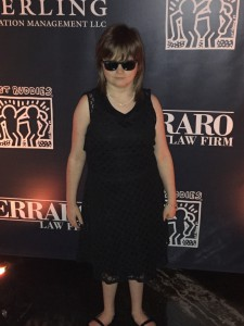 image of Marlana VanHoose standing in front of banner, wearing black sunglasses and fancy black dress