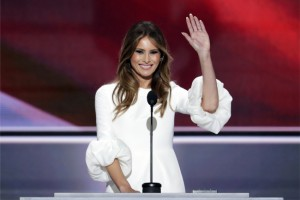 Melania Trump, in a white flowy dress, stands behind the podium waving.