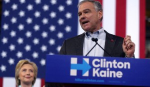 Tim Kaine standing behind podium, wearing black suit and light blue shirt, with Hillary Clinton smiling in the background