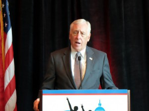 Rep. Steny Hoyer wearing a gray suit talking behind a podium