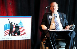 Rep. Jim Langevin seated in wheelchair wearing a black suit next to a podium with the text: #ABLE2WORK #ADA26