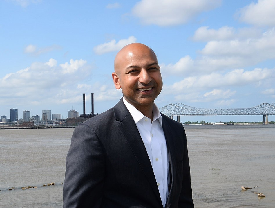 Abhay Patel standing and smiling facing the camera wearing a white dress shirt and black blazer with clouds, a bridge and water in the background