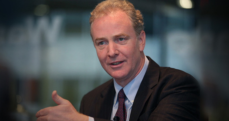Chris Van Hollen talking facing the camera wearing a suit waving his arm