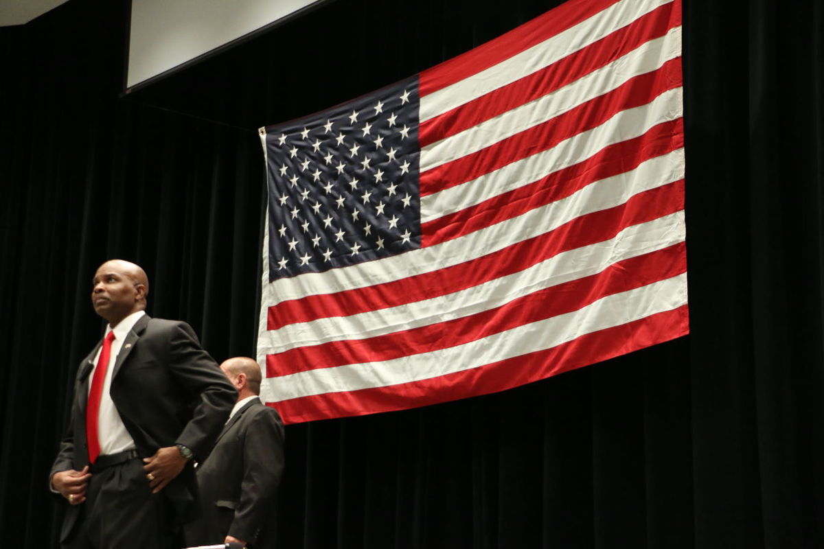 Dwight Young standing on a stage with a large American flag in the background