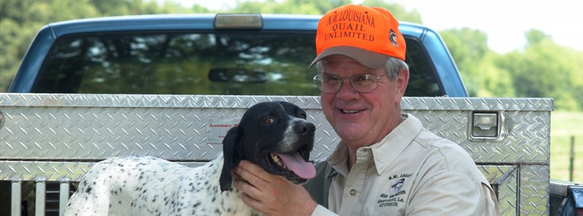 Foster Campbell poses for a picture with his dog while sitting in a pick-up truck