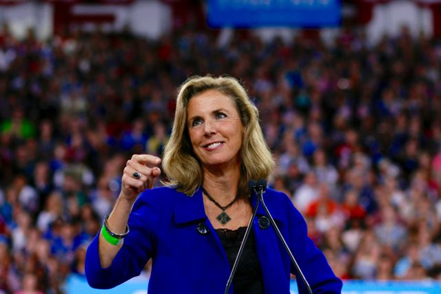 Katie McGinty speaking at a Hillary Clinton rally wearing a blue suit and large crowd behind her
