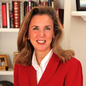Headshot of Katie McGinty wearing a red suit and white collared top in front of a bookcase