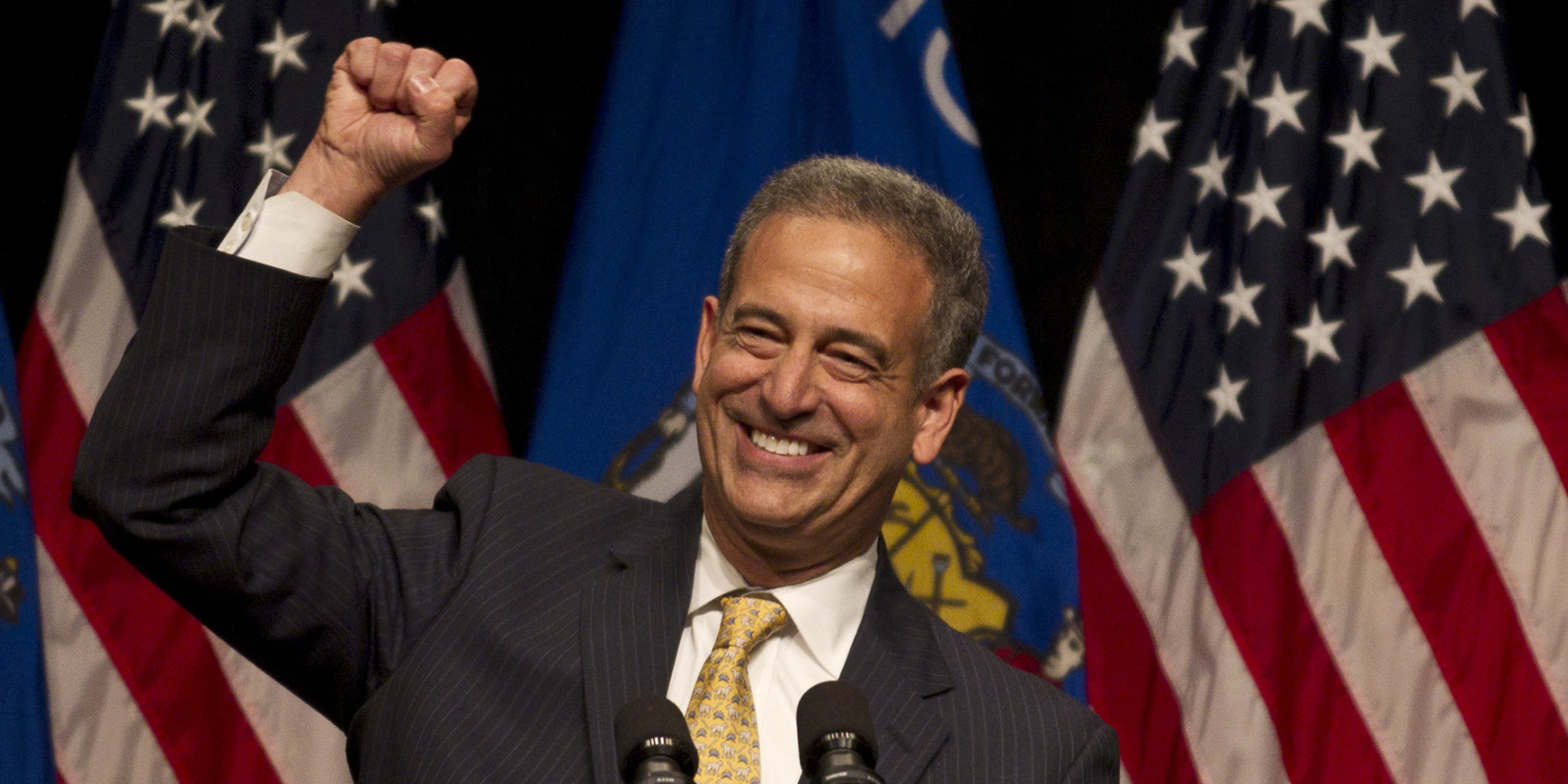 Russ Feingold smiling with a fist in the air while speaking at a campaign event. American flags in the background