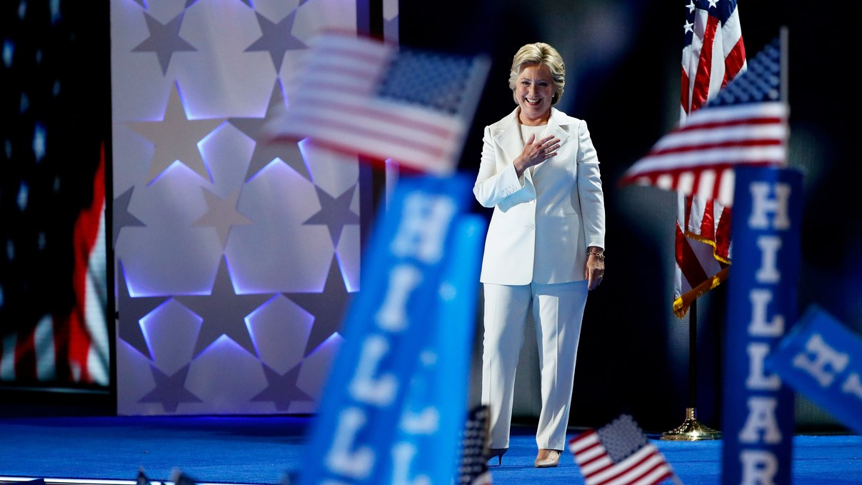 Hillary Clinton standing on stage with her hand on her heart, with Hillary signs and American flags waving in foreground