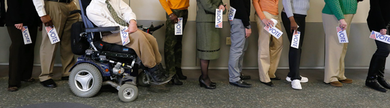 Image shows people in line waiting to vote. Majority are physically-able-bodied individuals standing in line. One man is in a power wheelchair.