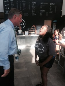 Burr speaking with a young woman with Down syndrome who works at Bitty and Beau's Coffee Shop