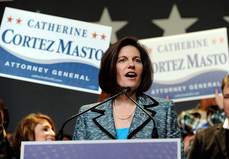 Catherine Cortez Masto speaking at a rally wearing a blue suit with signs saying her name behind her