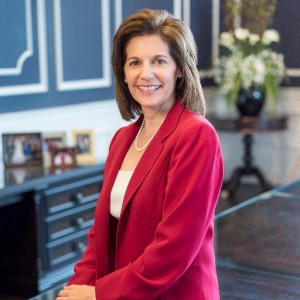 Headshot of Catherine Cortez Masto wearing a red blazer and white top with the backdrop of a formal living room