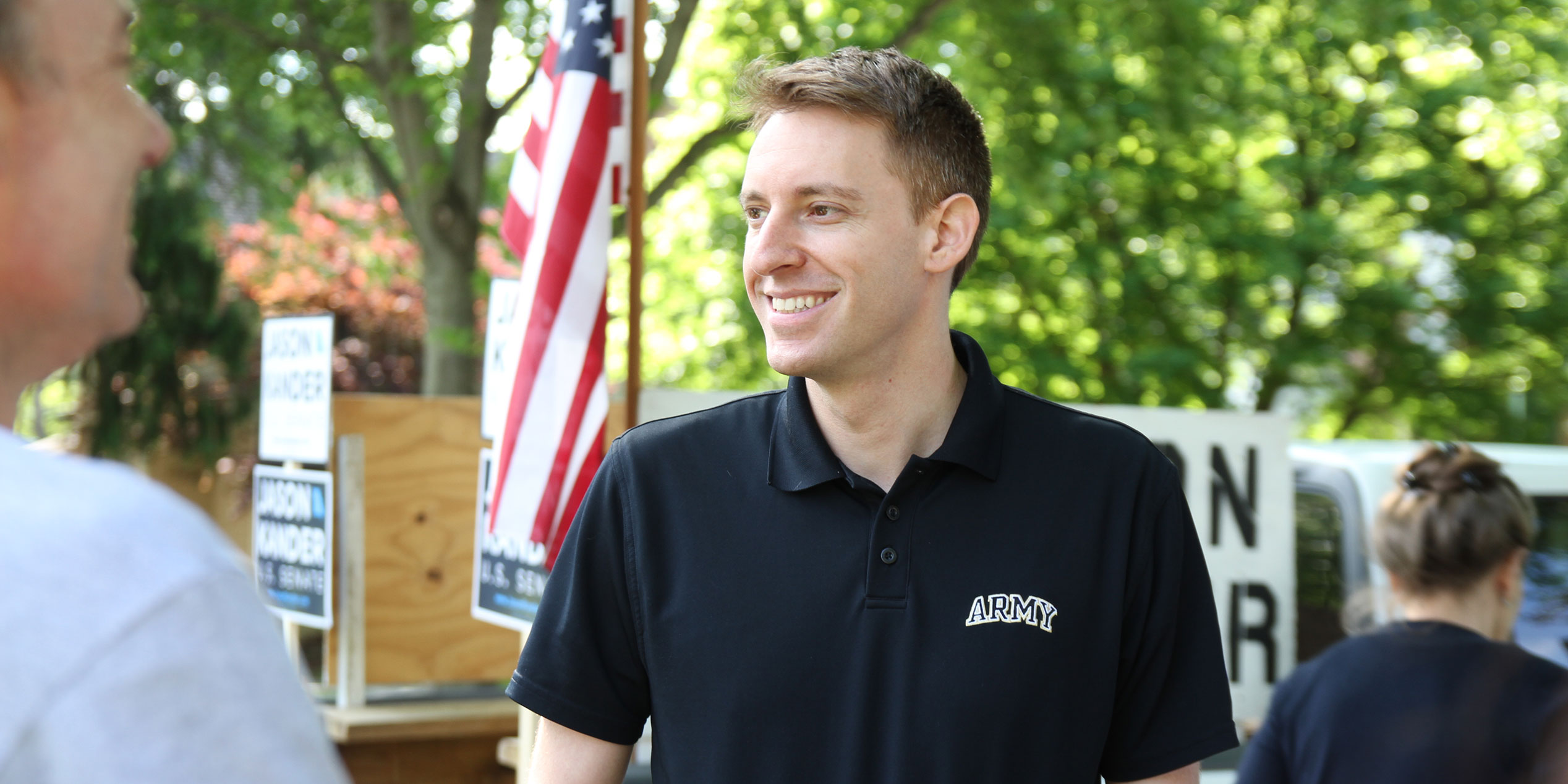 Jason Kander wearing an Army shirt standing outside with an American flag in the background