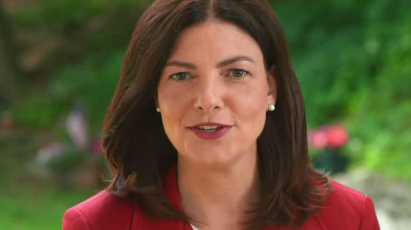 Kelly Ayotte headshot, outside, red suit