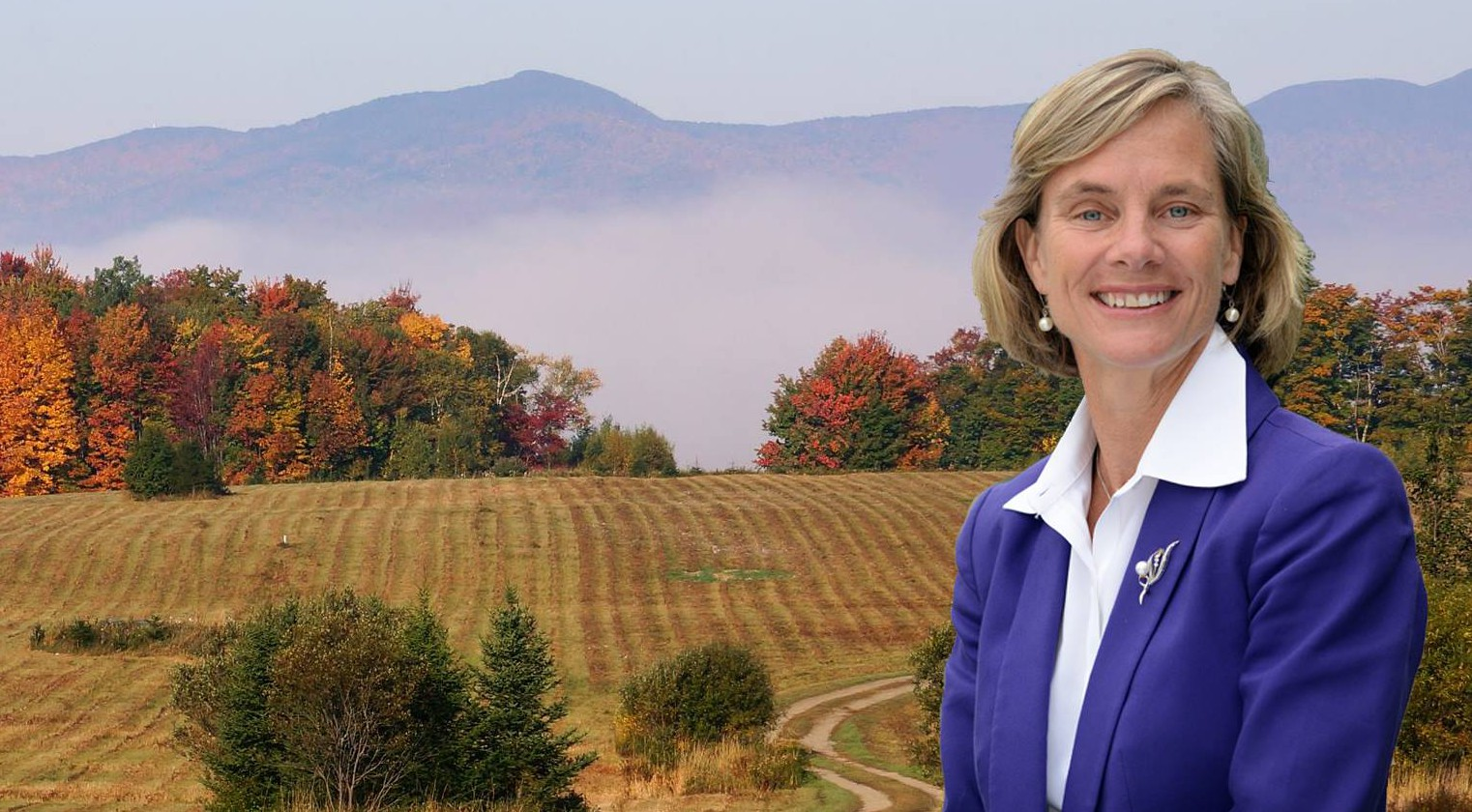 Sue Minter standing in a white shirt and blue blazer with a field behind her
