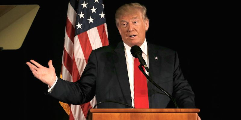 Donald Trump wearing a black suit, white shirt and red tie speaking behind a podium with a microphone and an American flag in background
