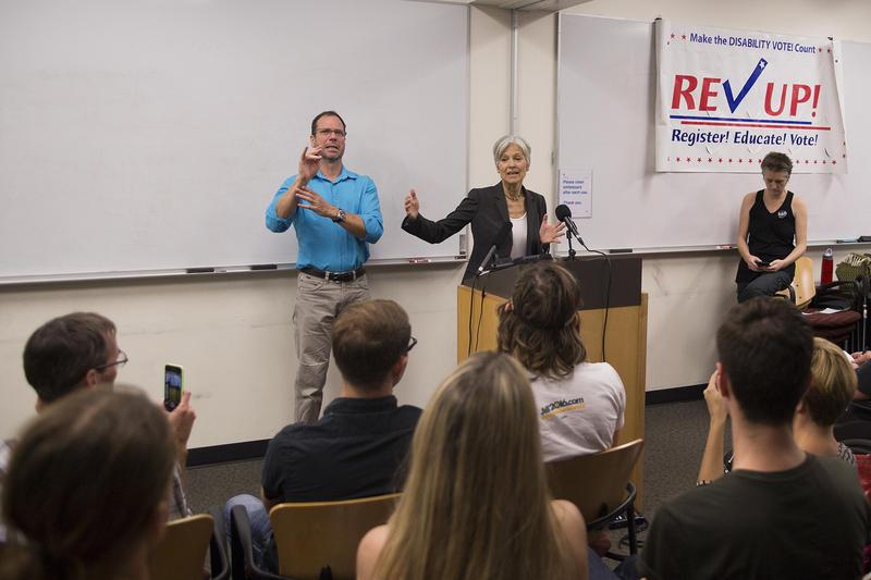 Jill Stein speaking behind a podium with an ASL interpreter standing next to her