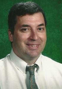 Joe DeMare headshot wearing a green tie with a green backdrop