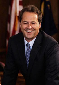 headshot of Steve Bullock smiling wearing a suit with white shirt and blue tie with American flag in background