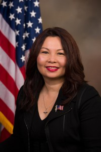 headshot of Tammy Duckworth with American flag in background