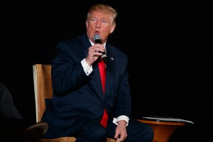 Donald Trump wearing a black suit, white shirt and red tie seated while holding a microphone and speaking