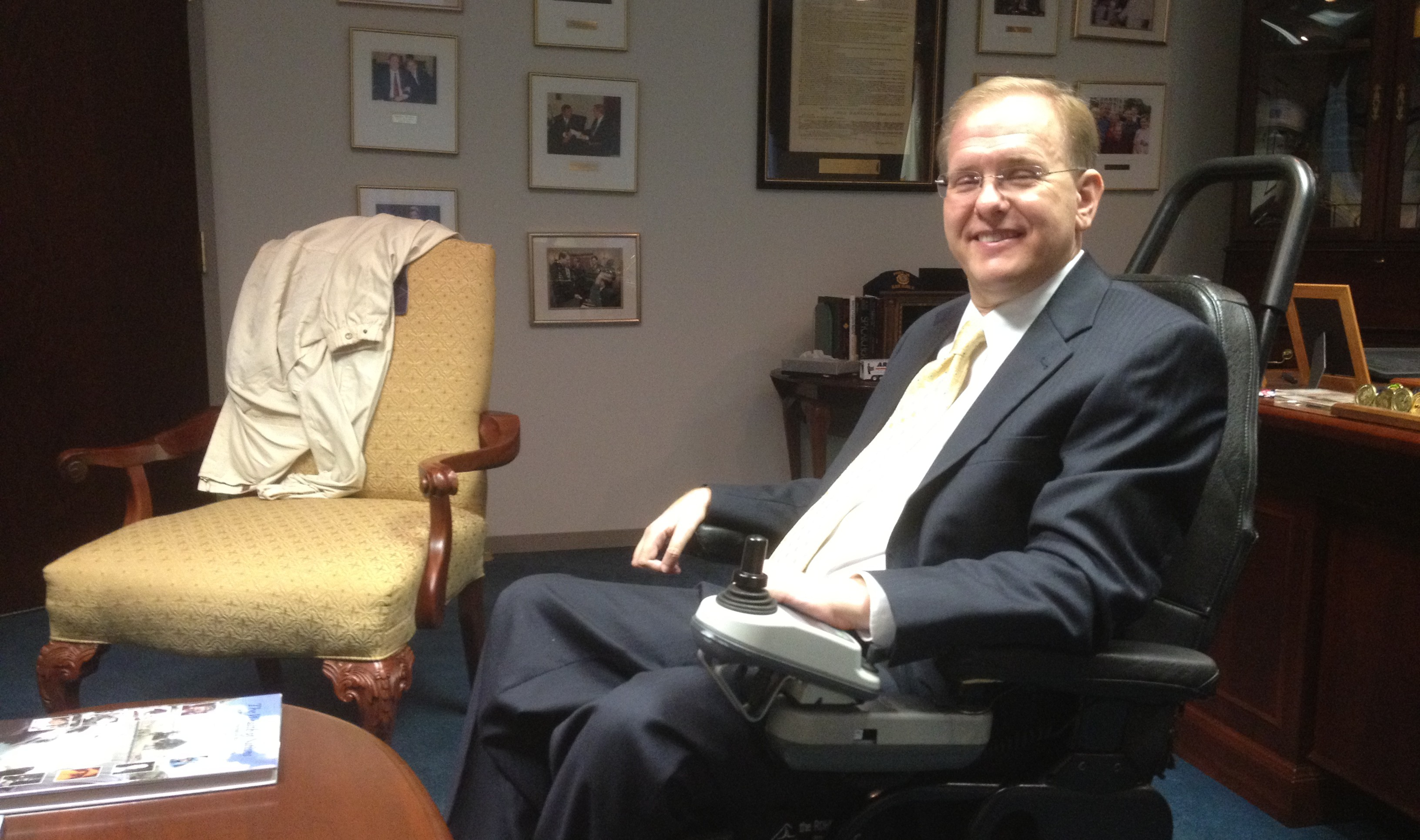 Jim Langevin seated in a power wheelchair in his office