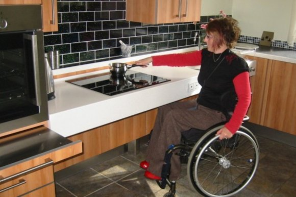 A young woman in a wheelchair using a stovetop in an accessible kitchen