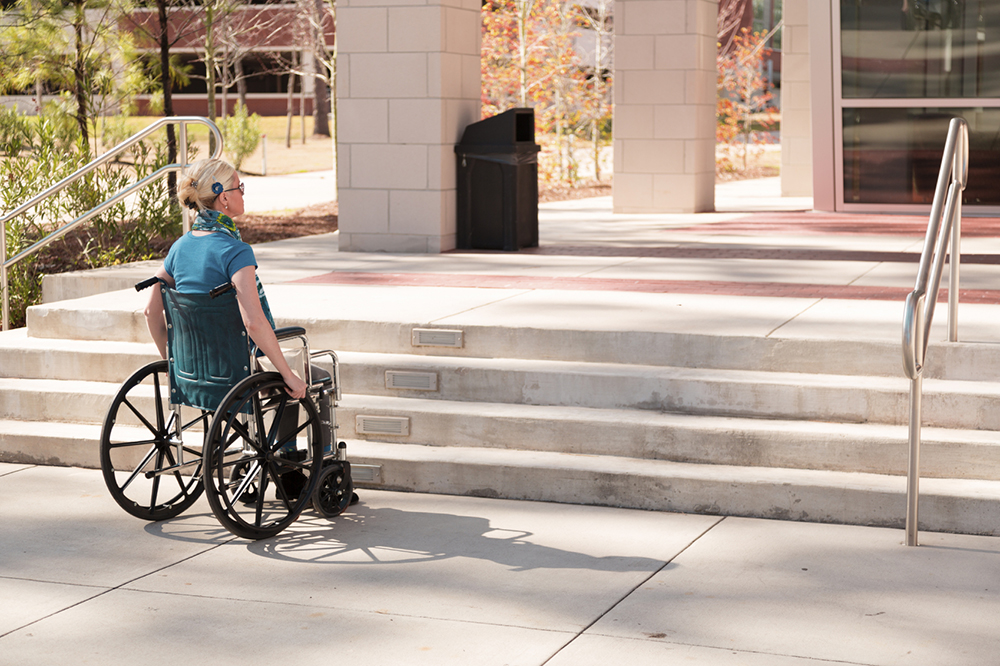 A young woman in a wheelchair looks up at in lack of an accessible entrance - only stairs