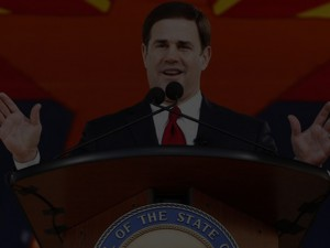 Gov. Doug Ducey speaking behind a podium