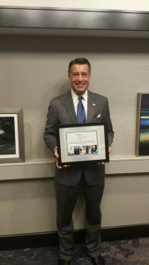 Governor Brian Sandoval holding an award from RespectAbility