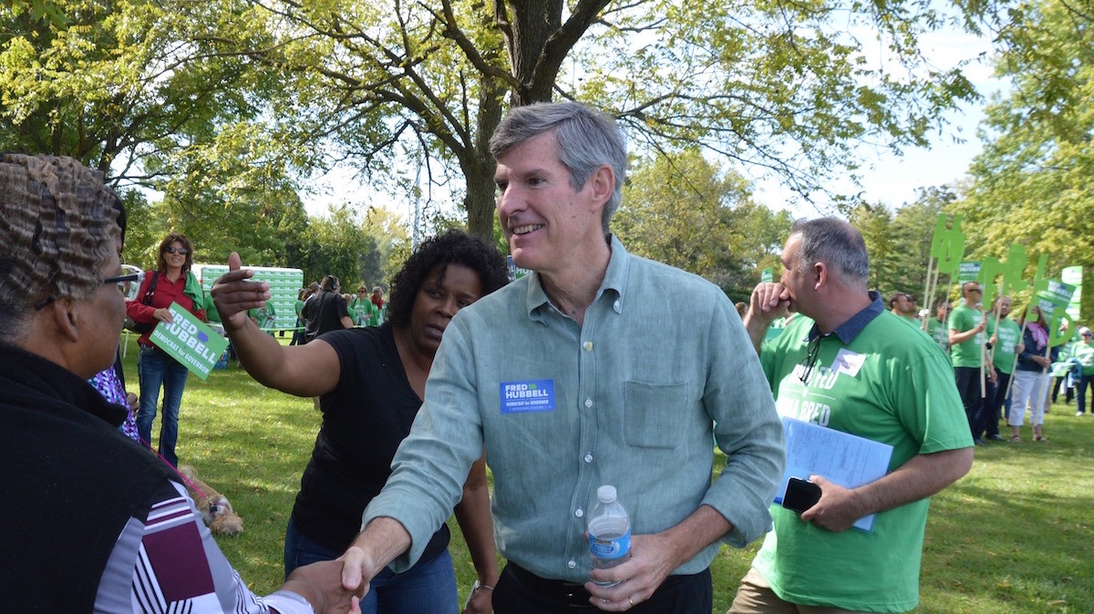 Fred Hubbell shakes hands with supporters in a park