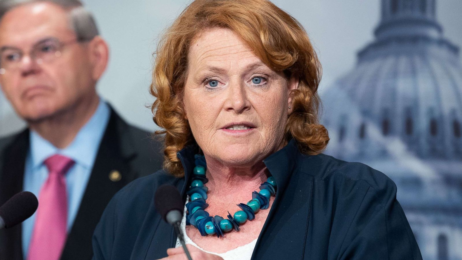 Heidi Heitkamp wearing blue suit, white top and blue necklace in front of U.S. Capitol backdrop