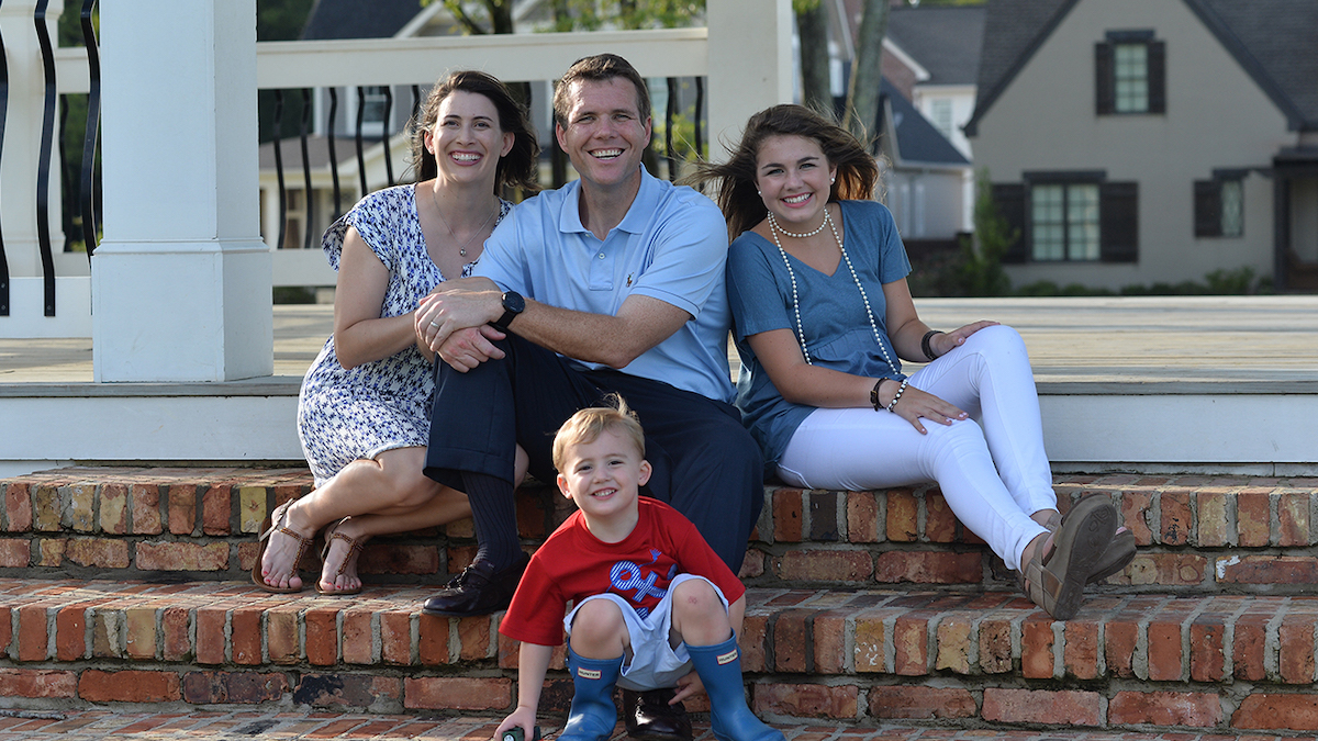Walt Maddox and his family sit and smile on steps to their house