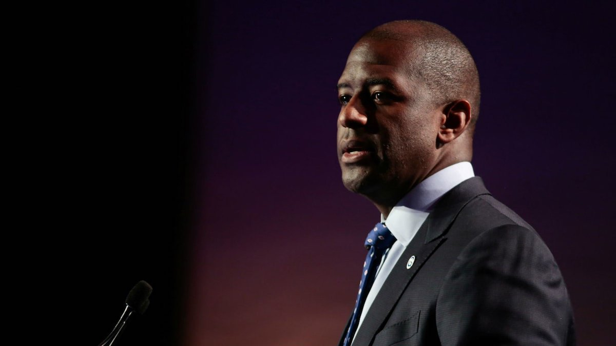 Gillum wearing a black suit, white top and black tie in front of red curtain
