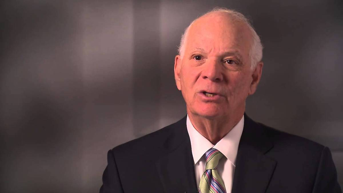 Ben Cardin speaking in front of a gray background