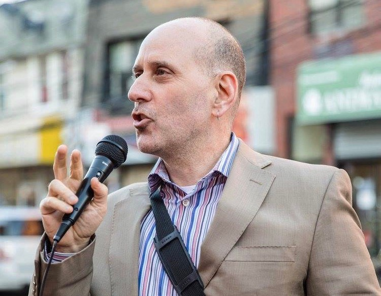 Harvey Epstein speaking into a microphone in front of a blurred background of storefronts in New York City