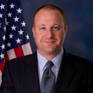 Jared Polis smiling in front of an American flag