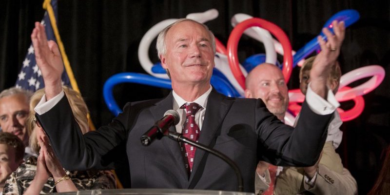 Asa Hutchinson speaks at his victory rally in front of supporters and balloons