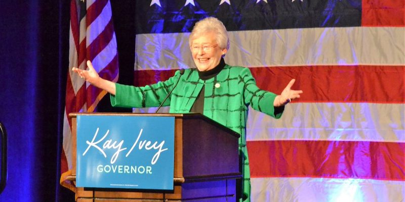 Kay Ivey speaks in front of an American Flag at her election night victory party