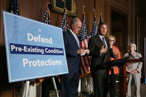 "Joe Manchin (D-WV) and other Democrats are standing in front of many American flags behind a podium speaking, next to a blue and white sign, which reads, ""Defend Pre-Existing Conditions Protections"""
